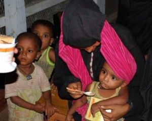 Administration of Plumpy'Doz in a CMAM program, Bangladesh. All watching, one eating (Source: UNHCR  Bangladesh)